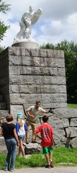 "Sandwich Historical Society director Adam Nudd-Homeyer acts out the 1941 collapse of the recently restored ""Niobe"" statue on the Great Wall of Sandwich..."